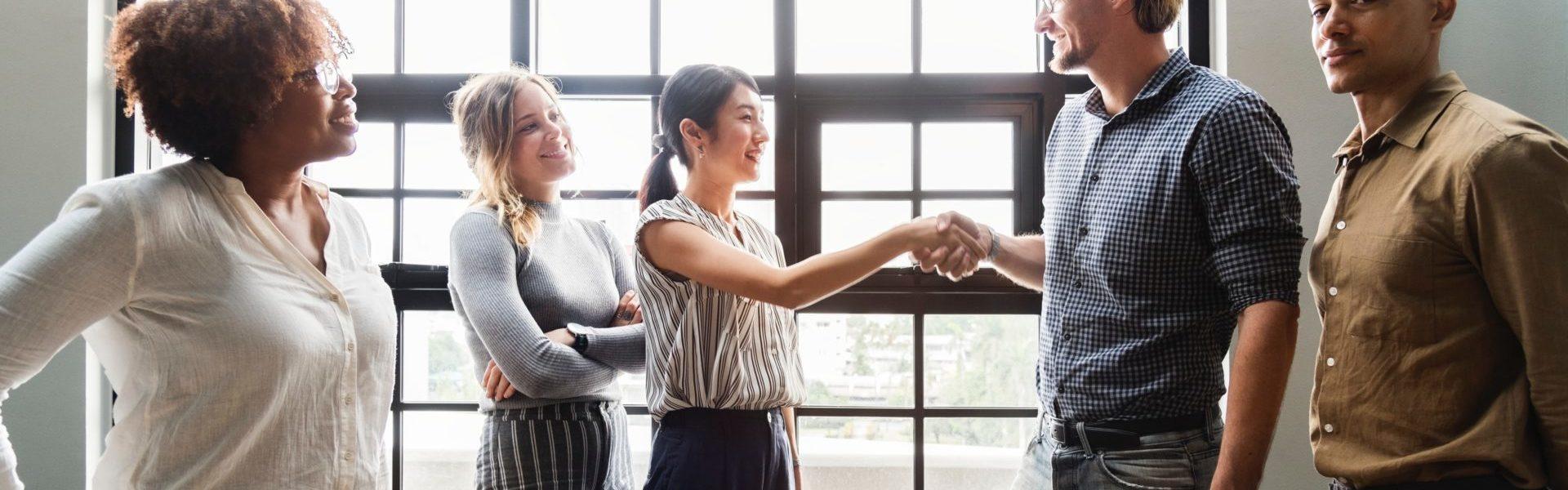 Personnes hommes femmes souriants se serrant la main dans une salle de réunion